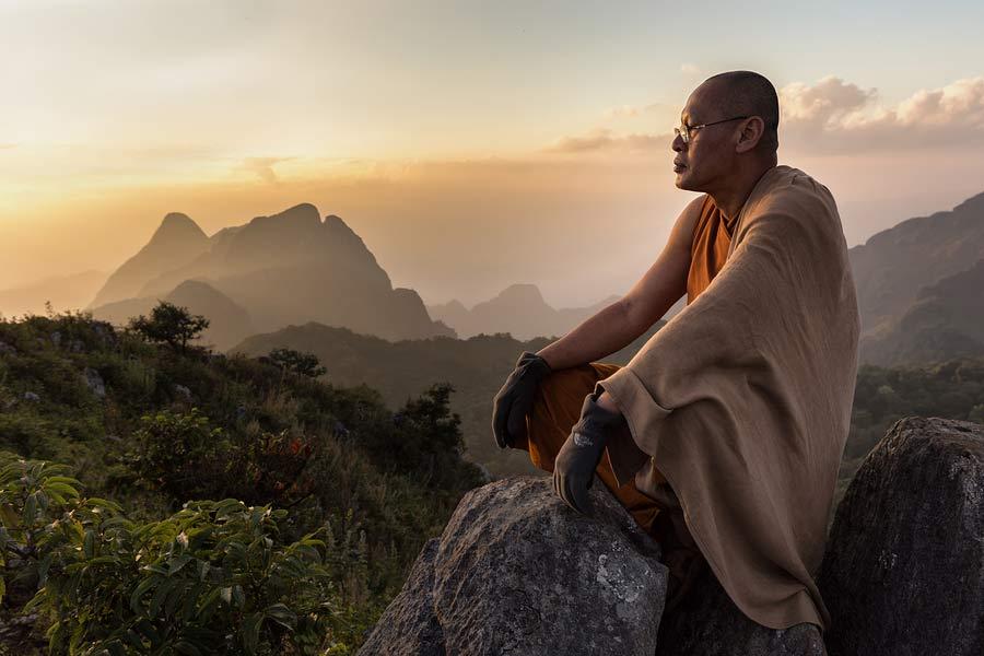 mnich sedící na vrcholku hory Chiang Dao