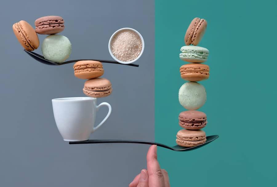 lžíce položená veprostřed na prstu , na každém konci je různé množství laskonek a kávy, vše ale drží v rovnováze