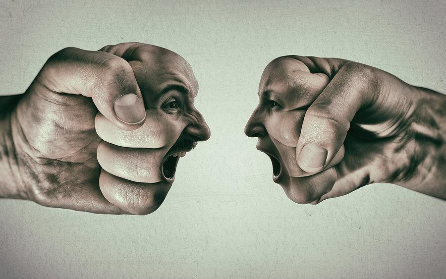fotomontáž dvou pěstí s tvářemi, které na sebe křičí