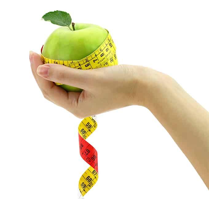 ženská ruka drží jablko ovinuté krejčovským metrem