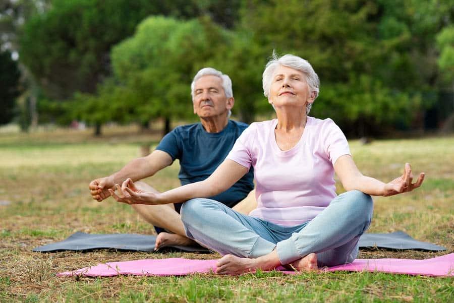 Senioři meditují v parku