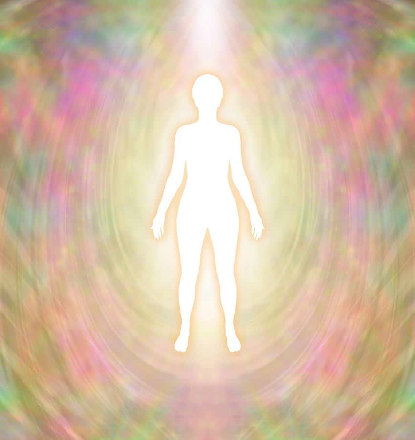 obrys lidské postavy obklopené aurou duhových barev