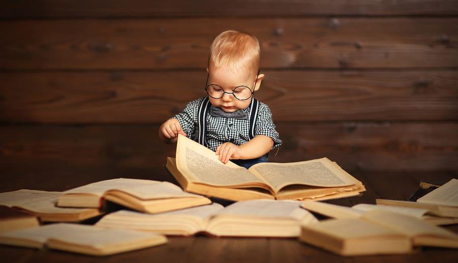 batole s brýlemi sedí mezi knížkami a čte