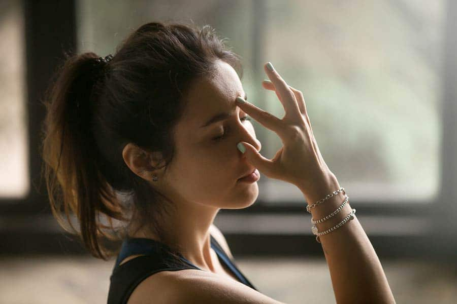 žena si přidržuje nosní dírku - praktikuje nadi shodhana