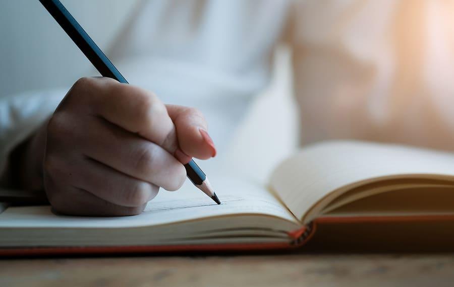 ruka s tužkou a knihou
