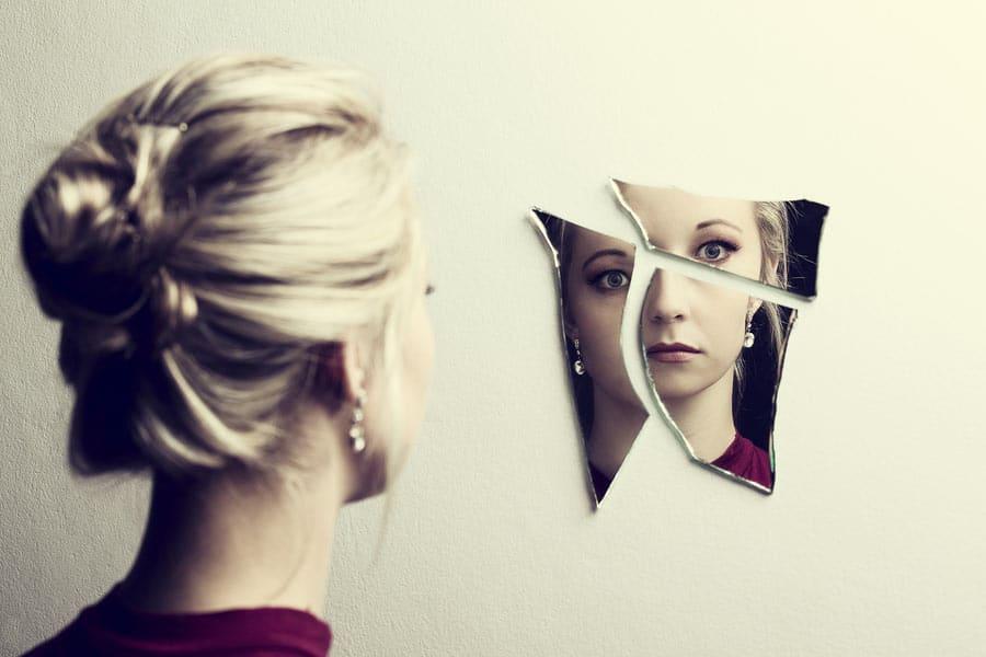 žena se dívá do svého odrazu v rozbitém zrcadle